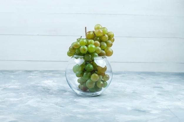 汚れた灰色と木製の背景のガラスポット側面図の緑のブドウ