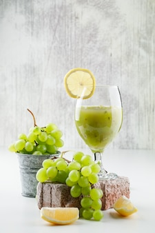 Зеленый виноград в мини-ведре с ломтиками лимона, кирпич, виноградный коктейль, вид сбоку на белой и шероховатой стене