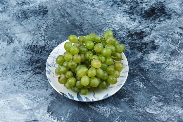 지저분한 석고 배경에 접시에 녹색 포도. 높은 각도보기.