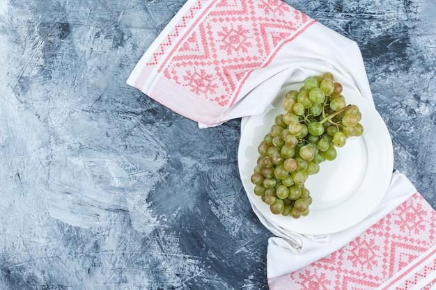 지저분한 석고와 주방 수건 배경에 흰색 접시 평면도에 녹색 포도