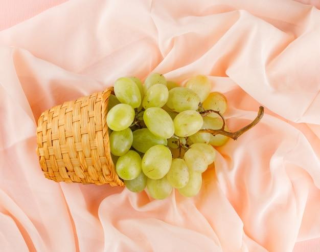 枝編み細工品バスケットの緑のブドウはピンクの繊維の上に横たわっていた