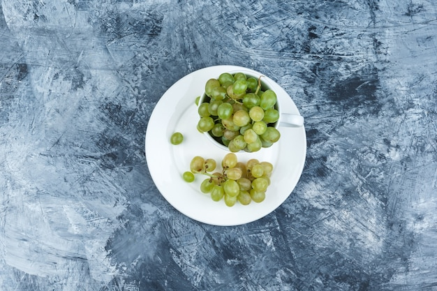 지저분한 석고 배경에 흰색 컵과 접시 평면도에 녹색 포도