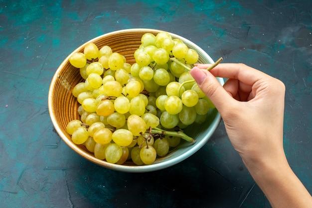 暗い背景の果物の新鮮なワインのまろやかなジュースで女性が取っているプレート内の緑のブドウ