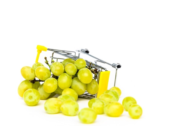 Green grapes in a miniature shopping cart on a white isolated background. buying grapes. copy space.