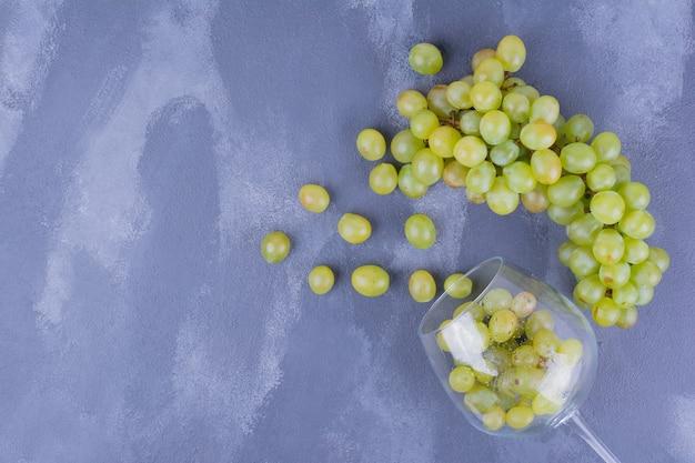 ワイングラスからの緑のブドウ