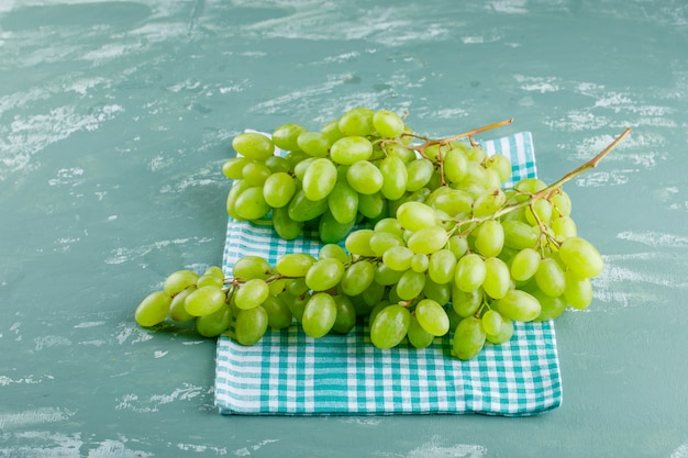 Green grapes on plaster and picnic cloth background, high angle view.