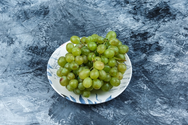 Uva verde in un piatto su uno sfondo di gesso grungy. vista ad alto angolo.