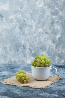 Green grapes in a white cup side view on grunge and piece of sack background