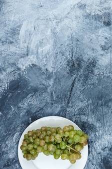 Green grapes in a white plate on a grungy plaster background. flat lay.