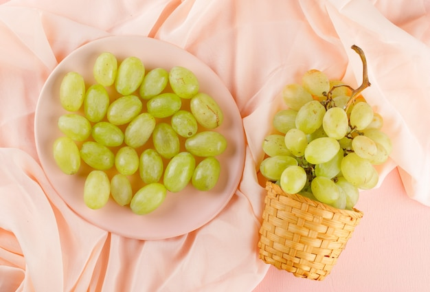 Green grapes in wicker basket and plate flat lay on a pink textile