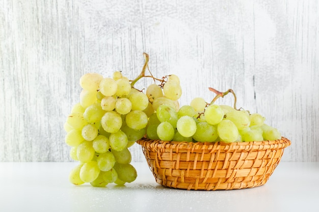 Green grapes in a wicker basket side view on white and grungy