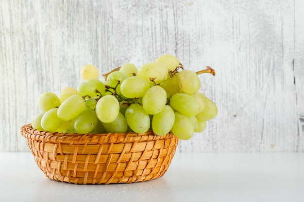 Green grapes in a wicker basket on white and grungy.