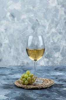 Uva verde con un bicchiere di vino vista laterale su intonaco grungy e sfondo tovaglietta di vimini