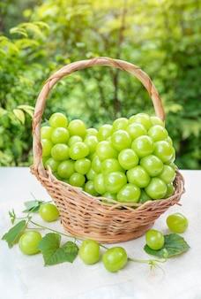バスケットに葉を持つ緑のブドウ