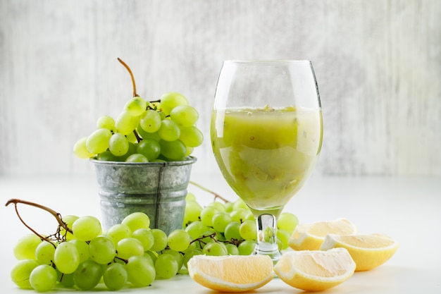Green grapes with lemon slices, grape cocktail in a mini bucket on white surface