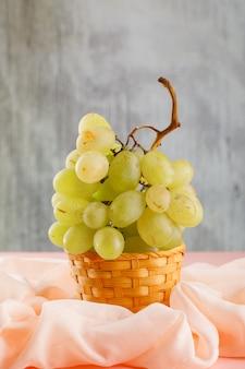 Зеленый виноград с текстилем в плетеной корзине на розовом и размытом,