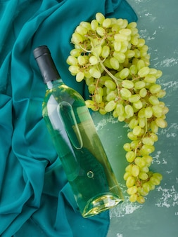 Green grapes with wine on plaster and textile,