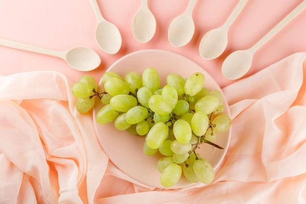 핑크와 섬유, 접시에 나무 숟가락과 녹색 포도