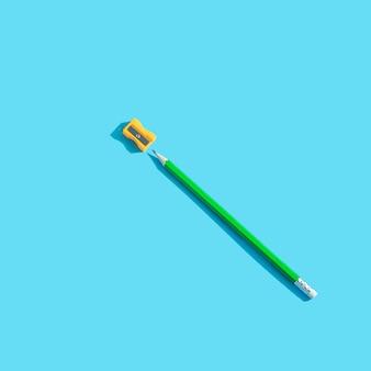 Зеленый графитовый карандаш с ластиком и оранжевой точилкой лежит на синем
