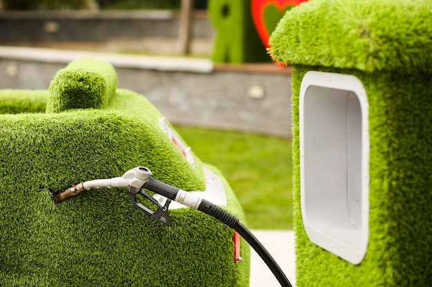 푸른 잔디 자동차와 주유소. 환경 보호, 깨끗한 공기 유지, 바이오 연료로 자동차에 연료 보급, 환경 친화적.
