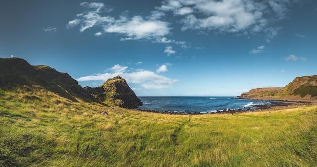 푸른 잔디는 바다 옆 초원을 덮었습니다. 북아일랜드 전경. 압도적인 수평선 배경입니다. 다양한 종류의 콜라주와 일러스트레이션을 만들기 위한 완벽한 이미지입니다.