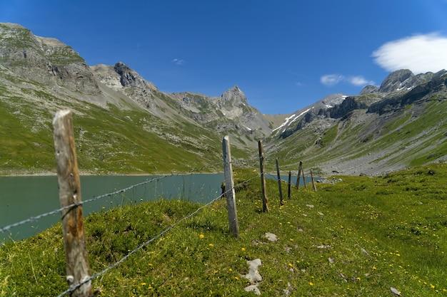 昼間の青空の下の山の近くの緑の芝生のフィールド