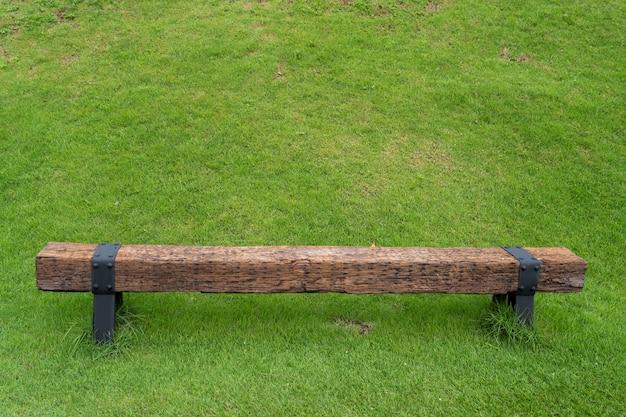 Поле зеленой травы со старой деревянной скамейкой