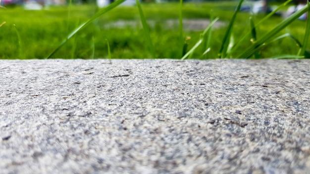 회색 콘크리트 벽 배경에 녹색 잔디, 고르지 않은 벽면 및 잔디, 배경 이미지. 배경 디자인을 위한 잔디 바닥 텍스처가 있는 회색 콘크리트 벽.