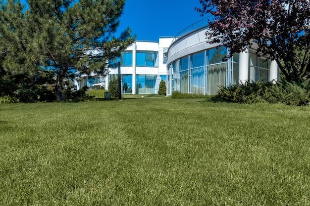 여름에 유리 벽이 있는 흰색 2층 맨션에 인접한 정원 잔디의 푸른 잔디