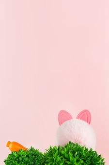 녹색 잔디, 토끼 귀, 당근은 분홍색 배경에 있습니다. 봄날 정원이나 초원.