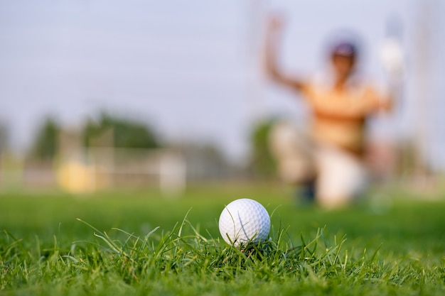 Green grass with golf ball close-up in soft focus at sunlight