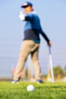 ゴルフボールのクローズアップと後ろがぼやけたゴルファーを持つ緑の草