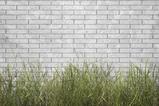 灰色のレンガの壁の背景と緑の草 Premium写真