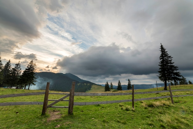 Green grassy valley slope with wooden fence and gate on woody foggy mountain under blue cloudy sky.