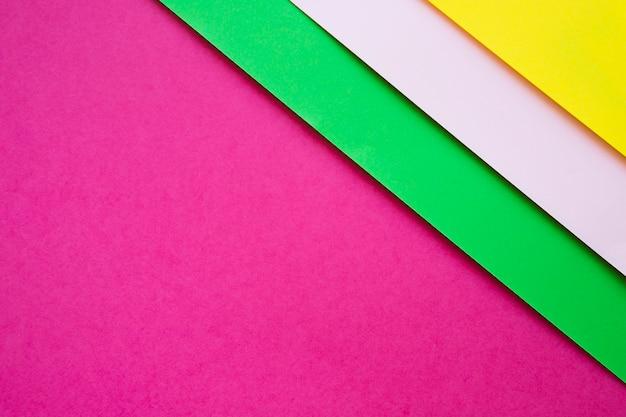 Verde; carte di cartone grigio e giallo su sfondo rosa