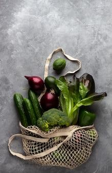灰色の表面のひも袋に入れた緑の食料品