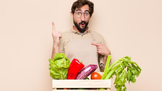 誇りと驚きを感じ、自信を持って自己を指さし、成功したナンバーワンのように感じている緑の食料品店の男性