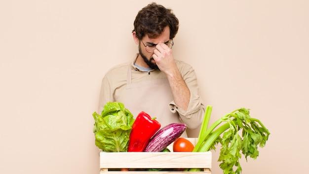 ストレス、不満、欲求不満、額に触れる、激しい頭痛の片頭痛に苦しむ緑の食料品店の男性