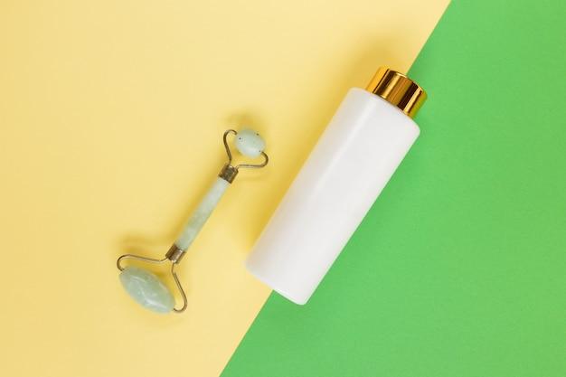 グリーングアシャフェイシャルマッサージツール。緑のクォーツ翡翠ローラーと黄色の化粧品ボトル。フラットレイ