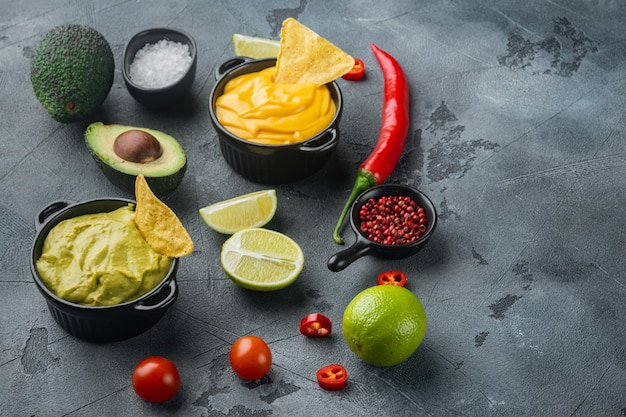 Green guacamole and yellow cheese dip sauce for traditional  mexican tacos, on gray table