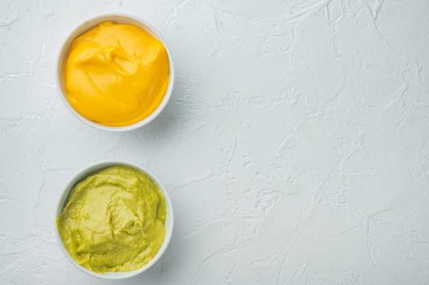 Green guacamole and yellow cheese dip sauce for traditional  mexican tacos, on white table, top view or flat lay