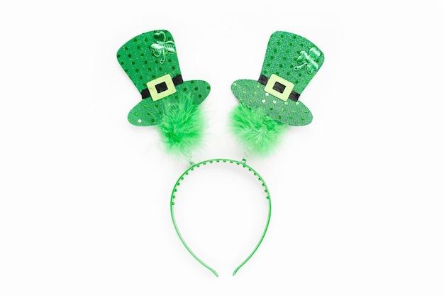 Обруч для зеленых волос со шляпами и листом клевера. реквизит для вечеринки в честь дня святого патрика на белом фоне. праздничная концепция. плоская планировка, вид сверху.