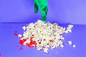 Green hand touching popcorn