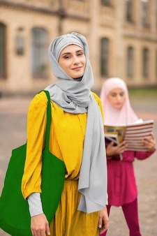 녹색 핸드백. 밝은 녹색 핸드백 서 친구 근처 밖에 서 세련 된 이슬람 여성