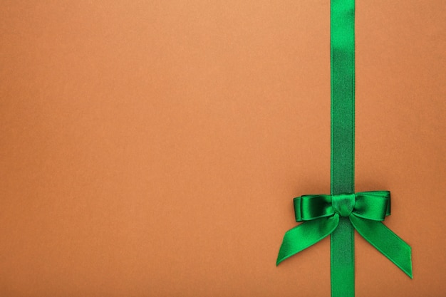 茶色の表面に弓が付いている緑の手作りリボン