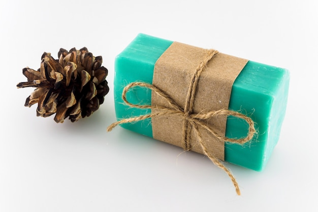 Green handmade soap and christmas tree cone on white background.