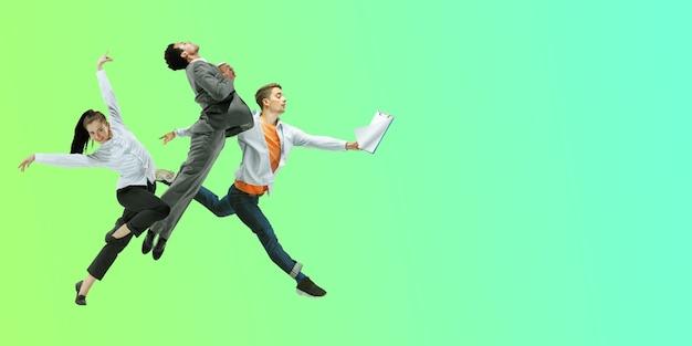 Зеленый. счастливые офисные работники прыгают и танцуют в повседневной одежде или костюме, изолированных на фоне градиентной неоновой жидкости. бизнес, запуск, рабочее открытое пространство, движение, концепция действий. творческий коллаж.