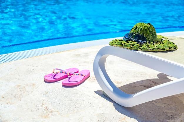 サンラウンジャーのサングラスとスイミングプールの近くのビーチサンダルとヤシの葉からの緑の帽子