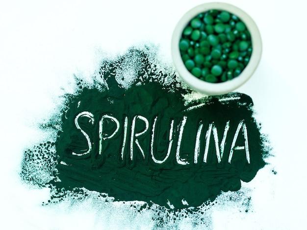 Green hawaiian spirulina in powder with inscription spirulina on light white background