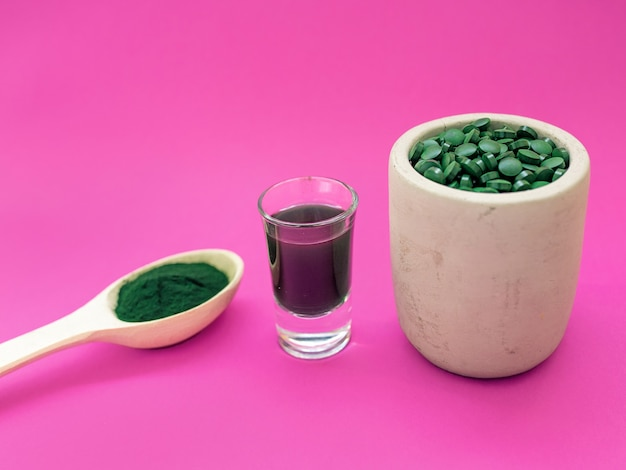Green hawaiian spirulina in tablespoons pills liquid beverage and powder on pink background
